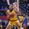 Basketball player holds the ball between her hands about to make a move as an opponent player hovers behind her.