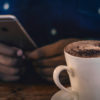A cup of coffee sits on on a table as someone uses their phone.