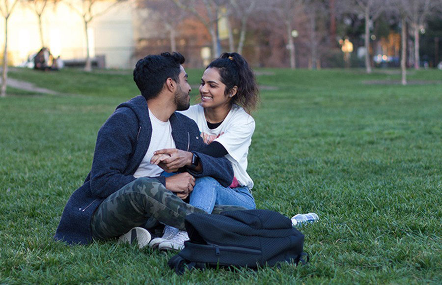 A couple sits on the grass and smiles at each other.
