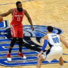 A basketball player bounces the ball as another prepared to block him.