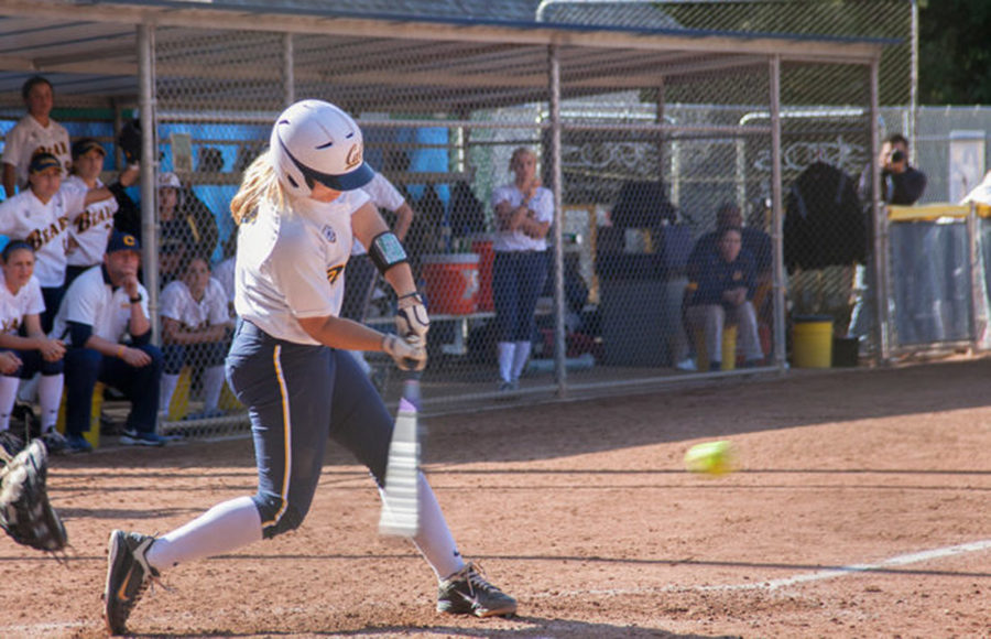 A softball player swings the bat to hit the ball.