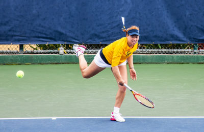 Tennis player strikes the ball with and watches it follow through.