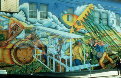 A mural on the side of a buildings depicts agriculture labor.