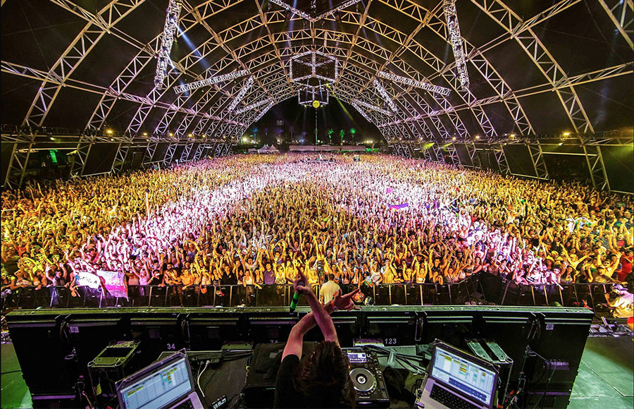 A DJ plays for a very large crowd that fills and entire arena.