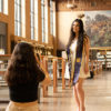 A photographer takes graduation photos for a girl in Doe Library