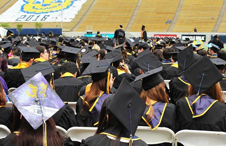 Berkeley graduates sit in their caps and gowns facing away from the camera.