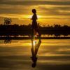 Silhouette of a person in a dress walking by a body of water during the sunset.