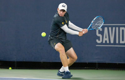 A tennis player swings his racket at the tennis ball.