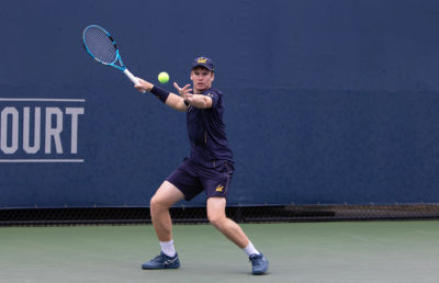 Mens tennis player receives the ball