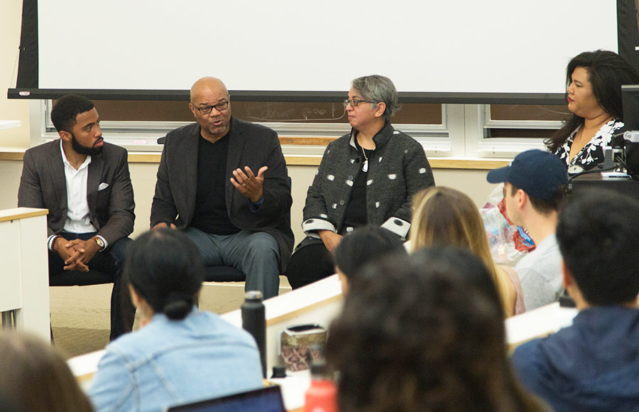 A panel of three speakers discuss in front of an audience.