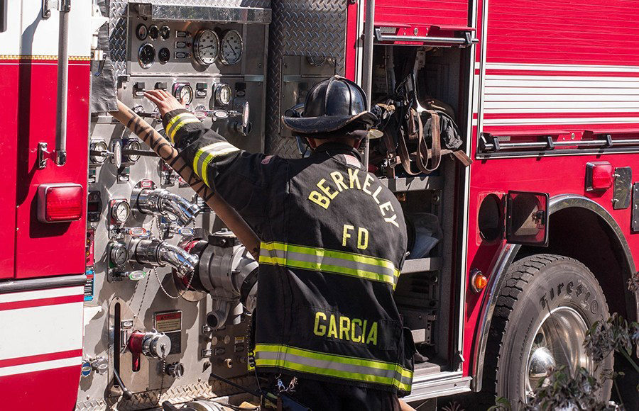 A firefighter reaches for a gauge on the side of the fire truck.