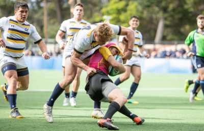 A rugby player is tackled by another athlete.