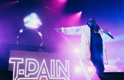 "A man performs on stage at the word ""T-Pain"" is projected behind him."