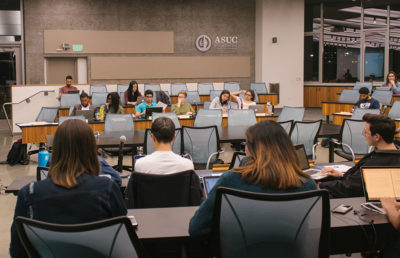 A group of people sit in large rows of desks in a meeting.