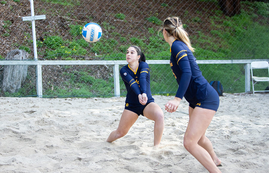 Two womens beach volleyball players receive a pass