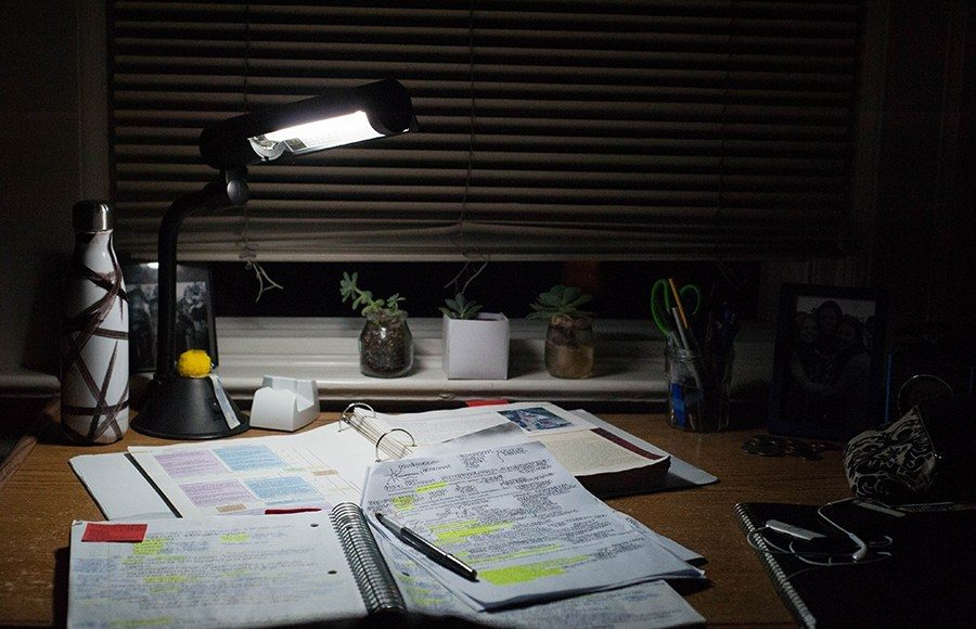 Student's desk covered with papers and study materials late at night