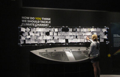 "Photo of an individual placing a note on a pinboard with the header, ""How Do You Think We Should Tackle Climate Change"", above it"