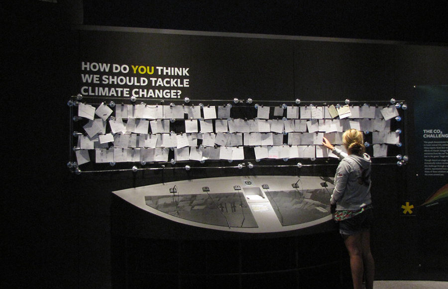 """Photo of an individual placing a note on a pinboard with the header, """"How Do You Think We Should Tackle Climate Change"""", above it"""