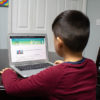 Photo of child on computer reading STEM materialw
