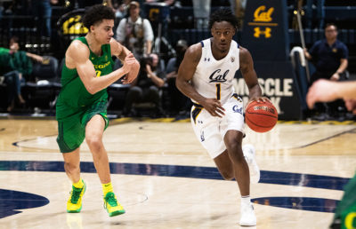 Photo of Joel Brown dribbling next to an Oregon defender