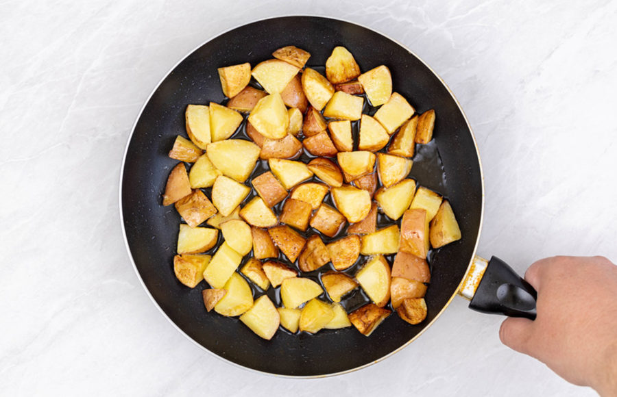 Photo of potatoes being cooked in a skillet