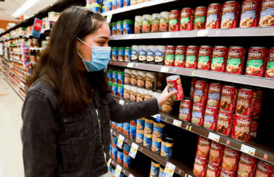 Photo of someone pulling a can of soup off a grocery shelf