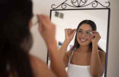 photo of a girl putting on eyeglasses