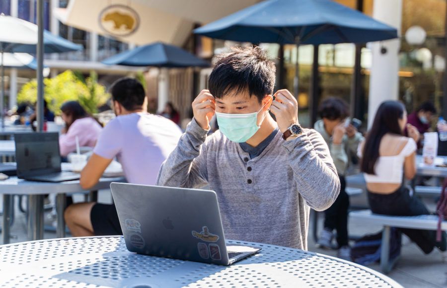 photo of someone putting on a mask while sitting at a cafe