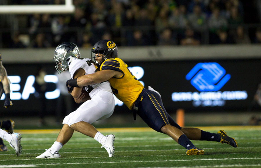photo of a Berkeley football player tackling someone during a game