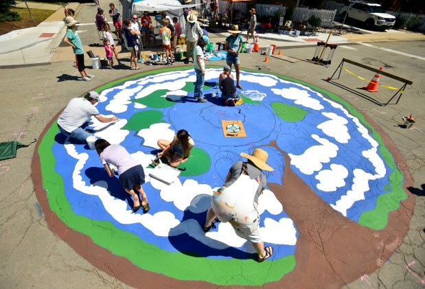 Local residents paint a mural in ...
