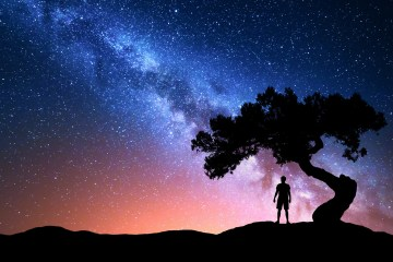 Human silhouette looking at the Milky Way galaxy at night