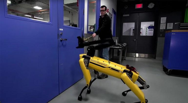 Boston Dynamics' SpotMini robot being hit with a hockey stick