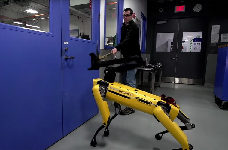 Boston Dynamics' SpotMini robot being hit with a hockey stick