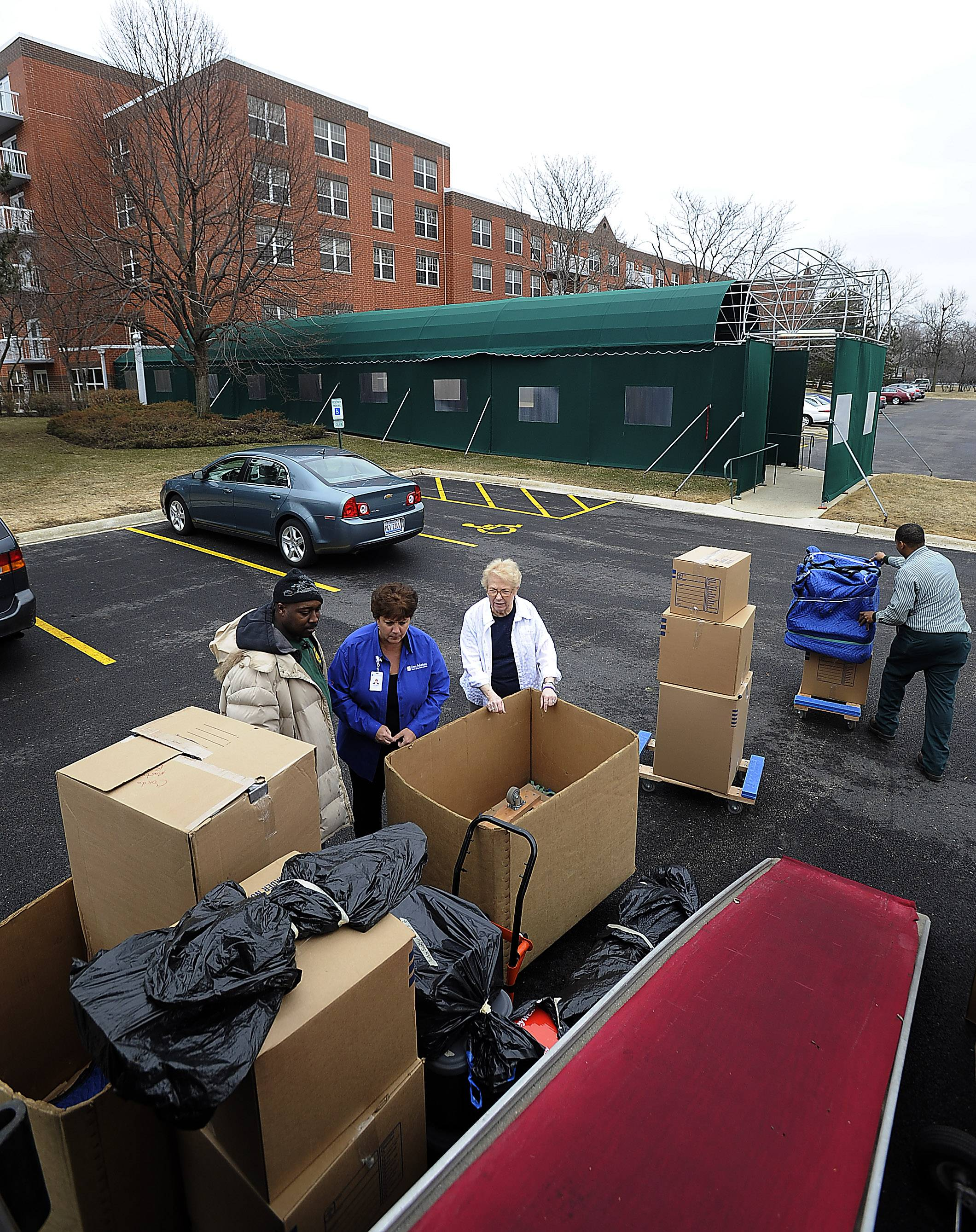 Gloria Bersani, director of Gero Solutions looks over the items of Martha Little (in white) along with Kevin Coleman of Moore Moving, as she moves into The Moorings in Arlington Heights.