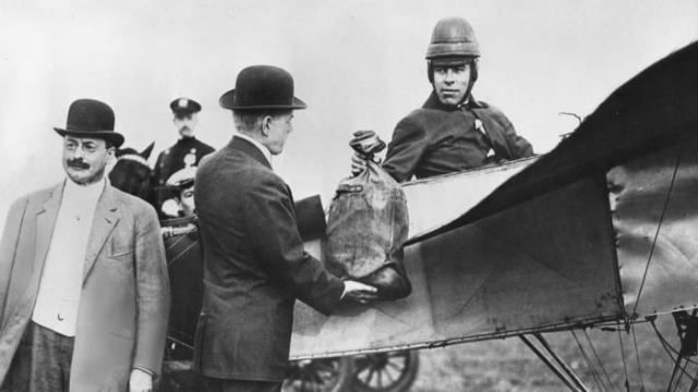 Earle Ovington, a pioneer aviator, flew the first air mail to the United States in 1911. United States Postmaster General Frank Hitchcock participated in the historic ceremony in Sheepshead Bay, New York when he delivered the first bag of mail to Ovington.