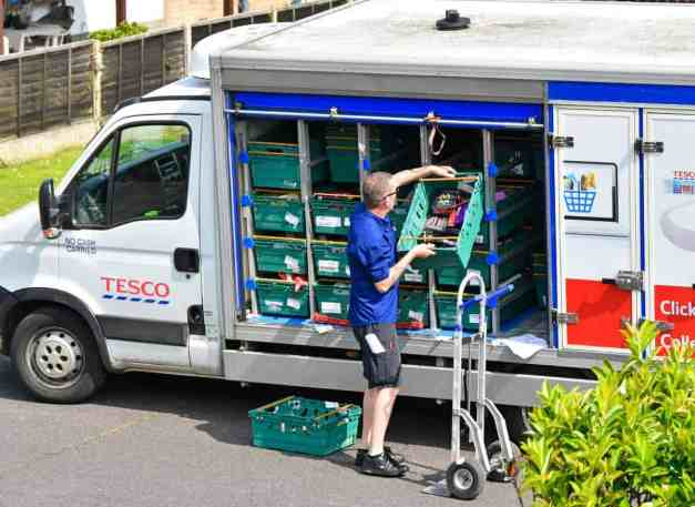 3_PAY_Delivery-driver-unloading-groceries-onto-trolley-home-delivery-street-address-from-Tesco-Supermarket