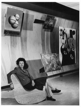 Berenice Abbott, Peggy Guggenheim in posa tra i dipinti surrealisti nella sua galleria Art of This Century di New York, 22 ottobre 1942. La collezionista calza scarpe firmate da Salvatore Ferragamo. AP/ ANSA