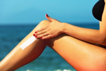 Handsome young female,applying sun tan cream,at the beach
