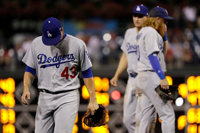 Los Angeles Dodgers relief pitcher Luis Avilan, left, walks off the field after being pulled during the eighth inning of a baseball game against the Philadelphia Phillies, Wednesday, Sept. 20, 2017, in Philadelphia. Philadelphia won 7-5. (AP Photo/Matt Slocum)