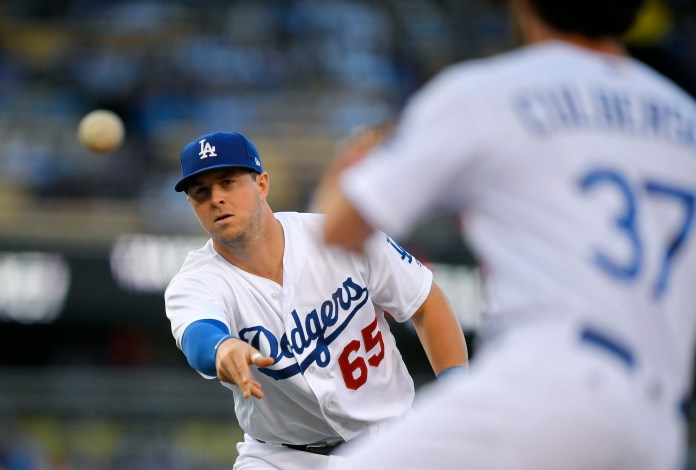 Los Angeles Dodgers first baseman Kyle Farmer, left, tosses the ball to second baseman Charlie Culberson to get San Francisco Giants' Joe Panik at first during the first inning of a baseball game, Saturday, Sept. 23, 2017, in Los Angeles. (AP Photo/Mark J. Terrill)