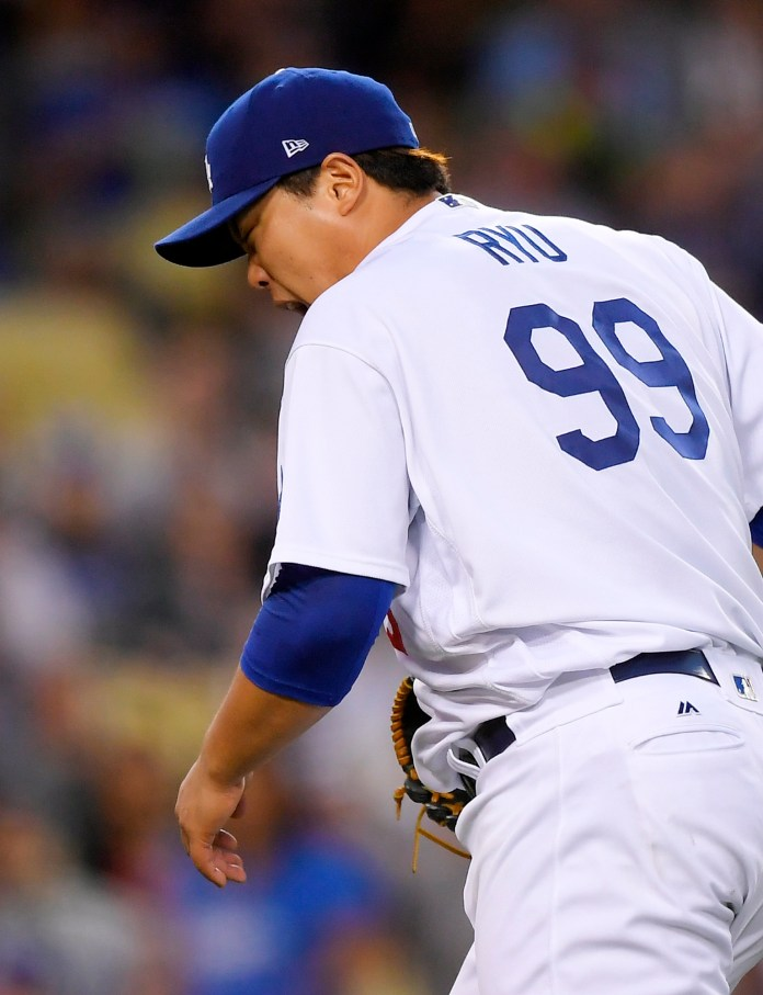 Los Angeles Dodgers starting pitcher Hyun-Jin Ryu, of South Korea, reacts after a ball hit by San Francisco Giants' Joe Panik struck him on the arm during the third inning of a baseball game, Saturday, Sept. 23, 2017, in Los Angeles. Panik was thrown out at first on the play. Ryu left the game. (AP Photo/Mark J. Terrill)