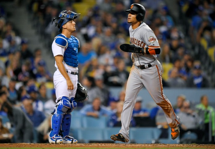 San Francisco Giants' Gorkys Hernandez, right, scores on a single by Denard Span as Los Angeles Dodgers catcher Austin Barnes stands at the plate during the fifth inning of a baseball game, Saturday, Sept. 23, 2017, in Los Angeles. (AP Photo/Mark J. Terrill)