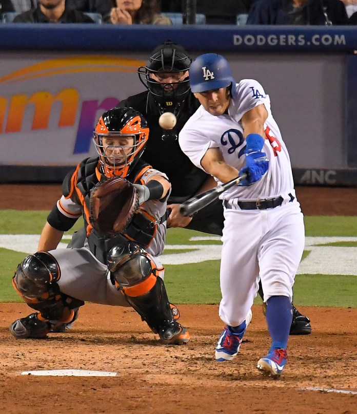 Los Angeles Dodgers' Austin Barnes hits a solo home run as San Francisco Giants catcher Buster Posey, left, and home plate umpire Mike Everitt watch during the eighth inning of a baseball game, Saturday, Sept. 23, 2017, in Los Angeles. (AP Photo/Mark J. Terrill)