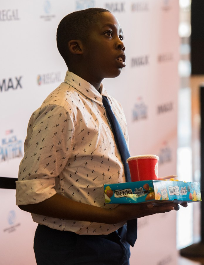 Chizzy Madu, 9, holds his popcorn and soda as he waits for fellow Boys & Girls Club members before they watch the Black Panther movie at a special Boys & Girls Club IMAX screening in Long Beach Thursday, February 15, 2018. As part of the viral #BlackPantherChallenge campaign, IMAX, Regal Entertainment Group, Walt Disney Pictures and Marvel Studios, hosted an advance IMAX screening of Black Panther for the Boys & Girls Club Long Beach. Club members got to see the film before its nationwide release. (Photo by Thomas R. Cordova / Daily Breeze)