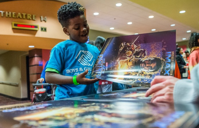 Richard Bass,7, gets his free poster after watching the movie Black Panther as the Boys & Girls Club members got to watch the Black Panther movie at a special Boys & Girls Club IMAX screening in Long Beach Thursday, February 15, 2018. As part of the viral #BlackPantherChallenge campaign, IMAX, Regal Entertainment Group, Walt Disney Pictures and Marvel Studios, hosted an advance IMAX screening of Black Panther for the Boys & Girls Club Long Beach. Club members got to see the film before its nationwide release. (Photo by Thomas R. Cordova / Daily Breeze)