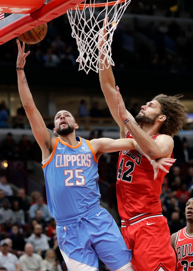 Los Angeles Clippers guard Austin Rivers, left, shoots against Chicago Bulls center Robin Lopez during the first half of an NBA basketball game, Tuesday, March 13, 2018, in Chicago. (AP Photo/Nam Y. Huh)