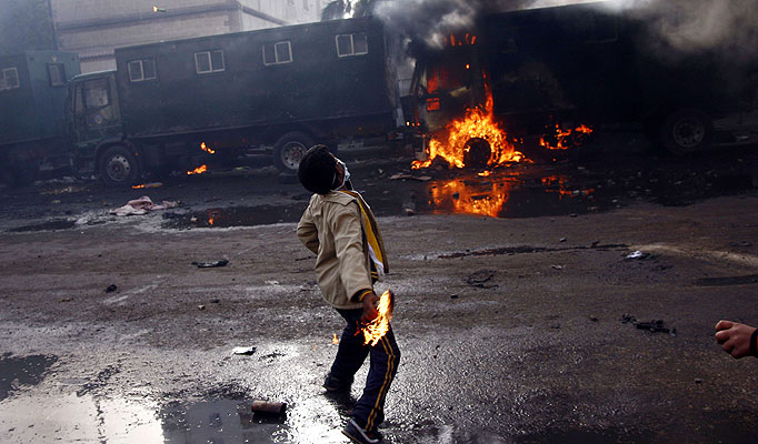 An Egyptian demonstrator throws a fuel bomb at police vehicles (AFP Photo)