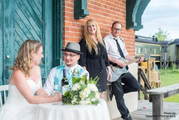 Bride and Groom sitting with people in background