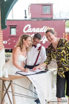 Bride and Groom laughing with officiant