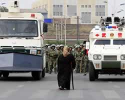 Seorang Muslimah Uighur menghadapi pasukan keamanan bersenjata Cina (REUTERS/David Gray)
